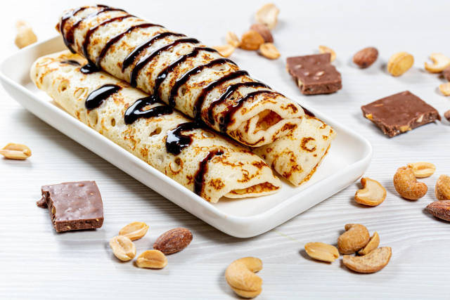 Homemade pancakes with chocolate topping and nuts