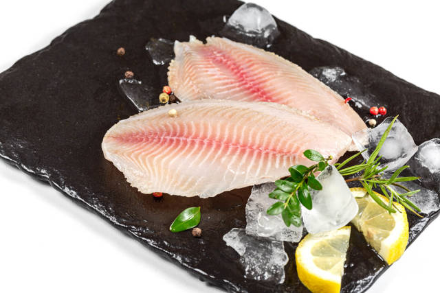 Fillet of tilapia fish with ice cubes on a black stone tray