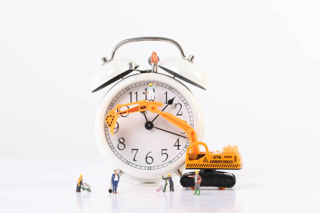Miniature workers wtih excavator and alarm clock on white background