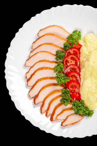 Pieces of chicken, tomato, green parsley and mashed potatoes