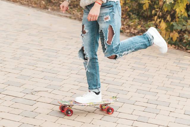 Woman skateboarding at autumn park