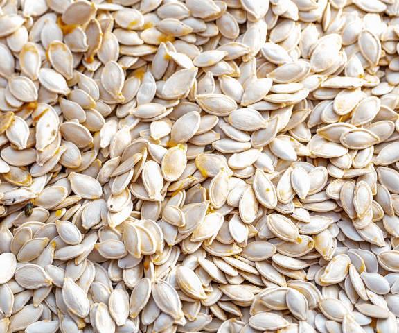 Raw pumpkin seeds background. Food texture
