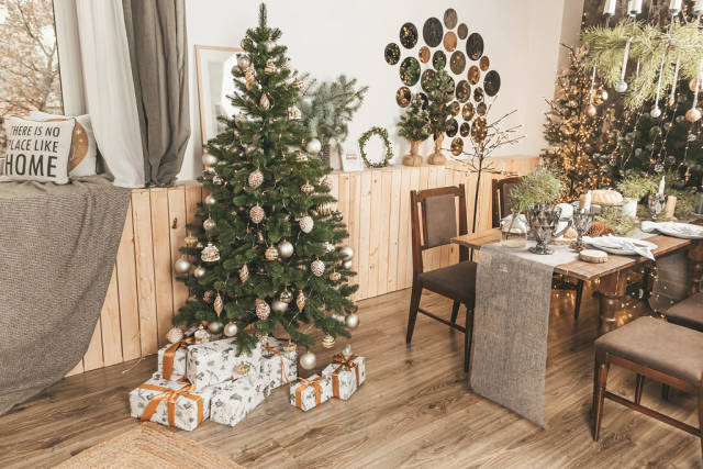 Christmas dinner with candles, table setting, decorated room with a christmas tree