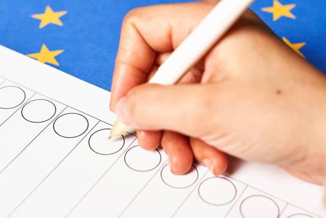 Hand eines Wählers mit dem Kugelschreiber macht ein Kreuz auf dem Stimmzettel vor der EU-Flagge