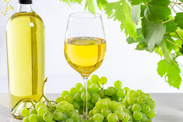 Wine background with ripe fresh grapes, full bottle and glass and green branches with leaves
