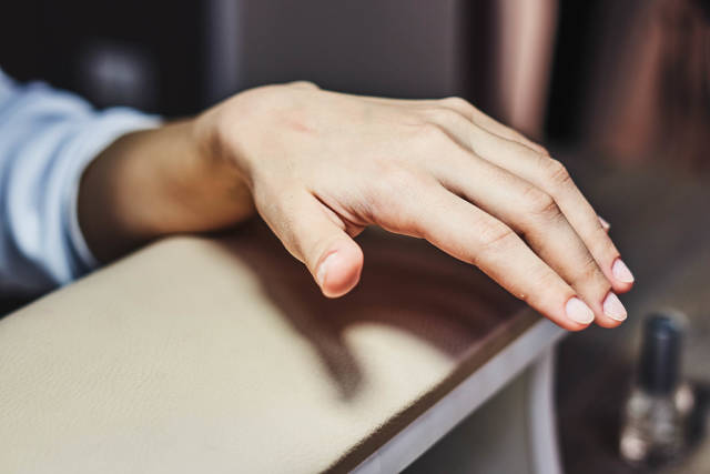 Woman holding her hand on manicure table