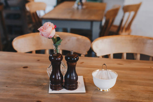 Cafe interior. Coffee table with rose in vase and sugar table