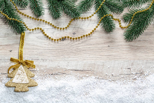Christmas tree branches, snow and golden Christmas decor on wooden background