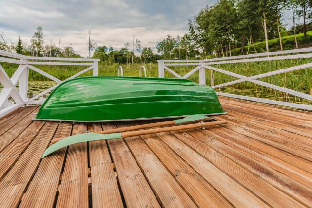 Grünes Ruderboot auf einem Bootssteg aus Holz