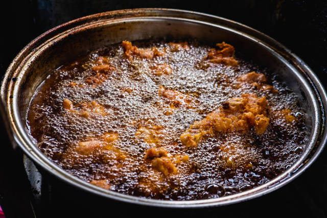 Chicken being cooked in a deep fry pot