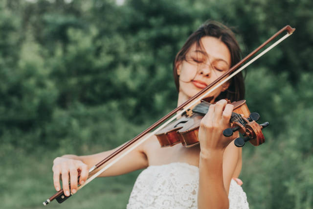 Girl playing on the violin outdoors in summer day