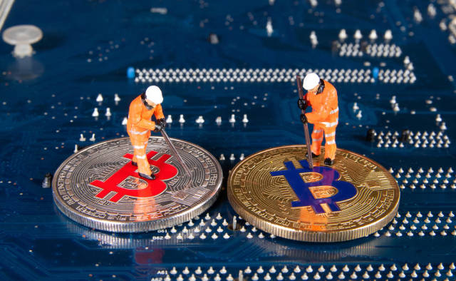 Two miners figures standing on a Bitcoins