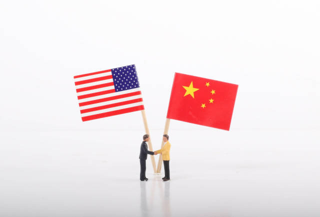 Two businessman shaking hands in front of flags of USA and China on white background
