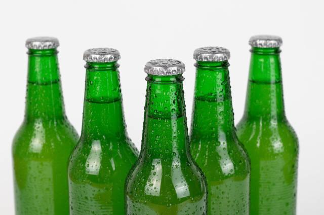 Reihe von Bierflaschen vor weißem Hintergrund