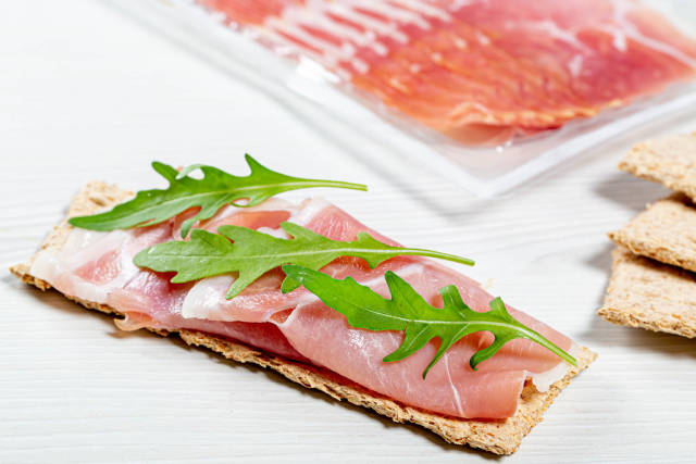 Sandwich with crispbread, dry-cured ham and arugula