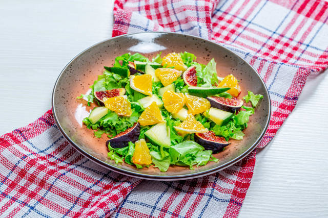 Low-calorie salad with fresh lettuce, oranges, figs and mango. The concept of vegetarianism, weight loss