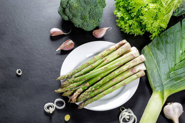 Asparagus, lettuce, broccoli, leeks and garlic on black background. Top view