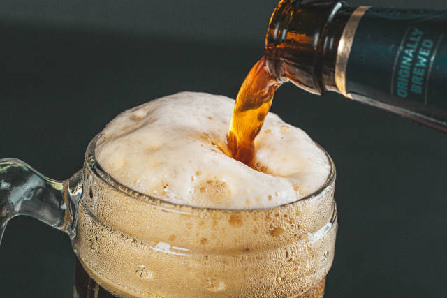 Dark fresh beer poured into glass, close up