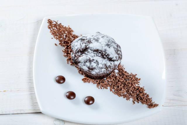 Fresh chocolate muffin with chocolate chips and powdered sugar