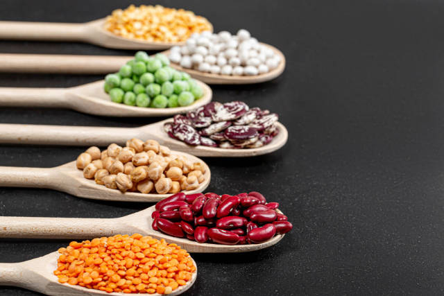 Assortment of legumes in wooden spoons on black background