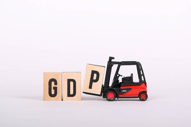 Toy forklift holds wooden letter block P to complete word GDP on white background