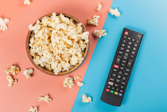 Top view, bowl of popcorn with tv remote control on pink and blue background