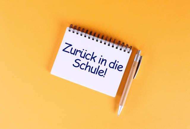 Top view of notebook with Zurück in die Schule text on orange background