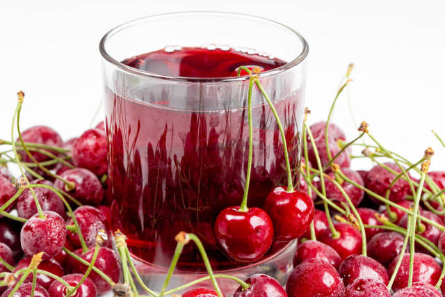 Glass of cherry juice with fresh cherry berries