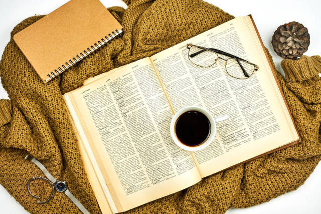 A book and cup of black coffee on a knitted brown sweater