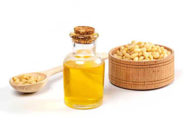 Oil in a bottle with pine nuts in a wooden spoon and in a bowl on a white background