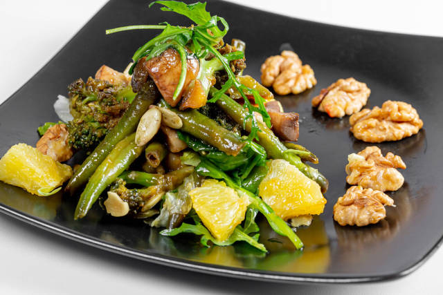 Vegetarian salad with asparagus, broccoli, lettuce, arugula, orange and walnuts