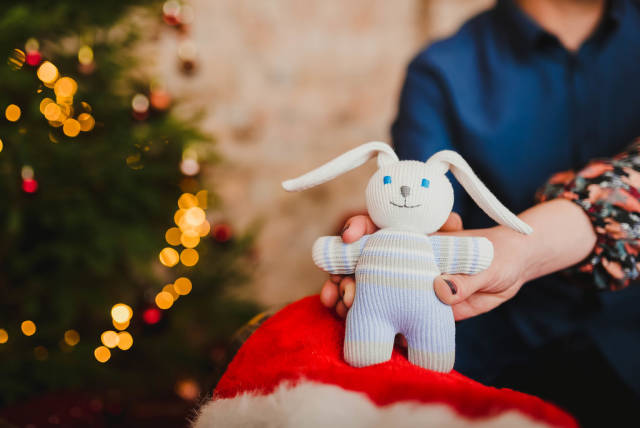 Little Christmas Bunny Toy With Lights On Background