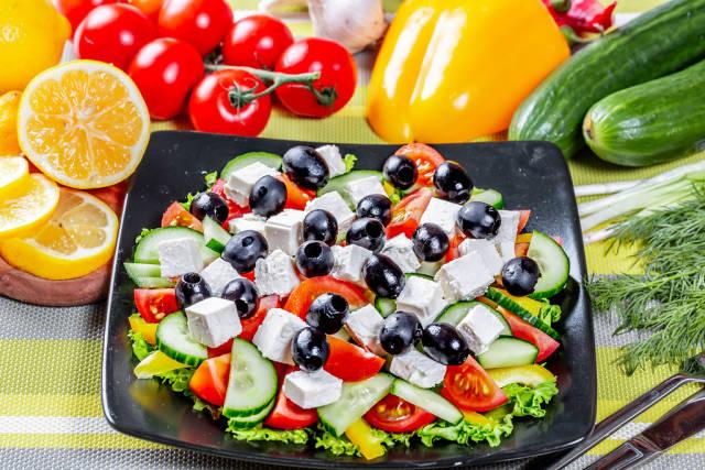 Blick von oben auf Teller mit griechischem Salat mit Oliven und Fetakäse umgeben von Gemüse