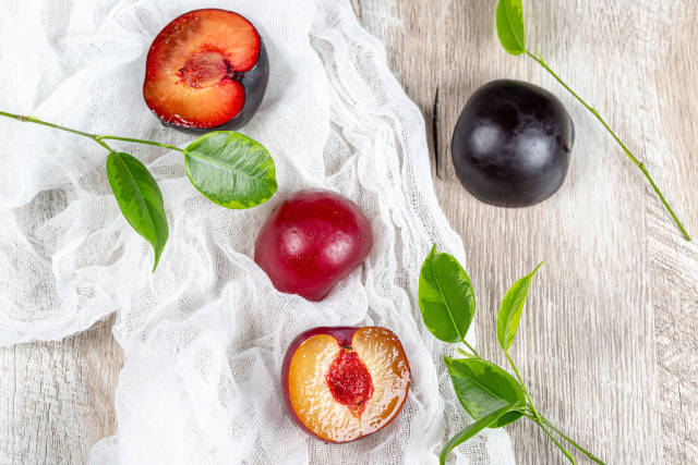 Top view, fresh plums with leaves on a grey wooden background