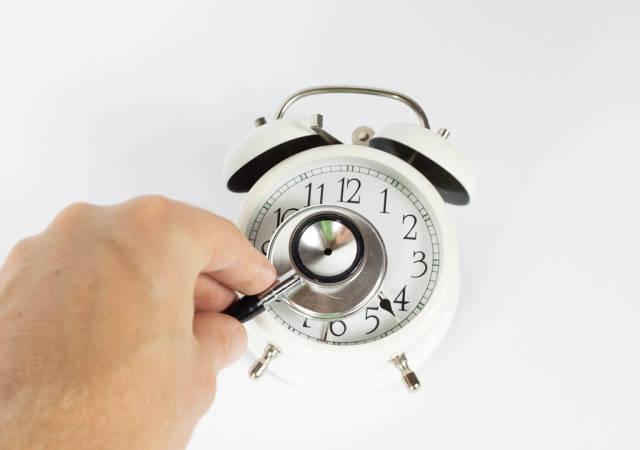 Stethoskop und Uhr vor weißem Hintergrund