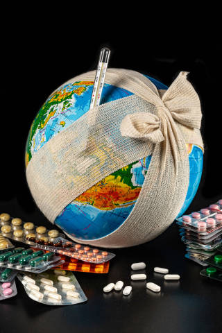 A globe in a bandage, with a thermometer and pills - the concept of global diseases and pandemics
