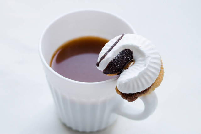 A cup of coffee and a cookie with a cream