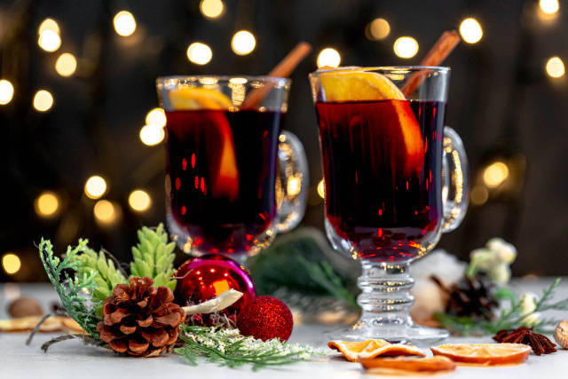 Two glasses of mulled wine with christmas decor and glowing garland background