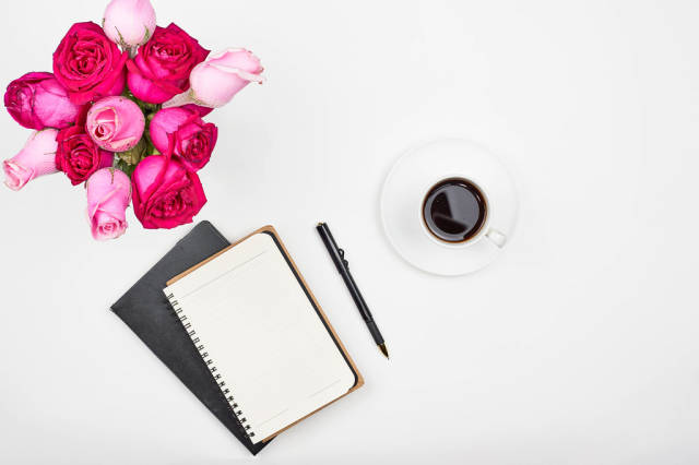 Modern feminine working place with coffee and roses. Work from home concept