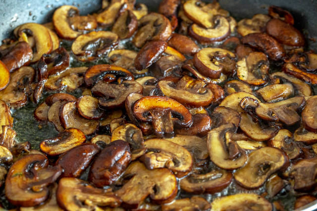 Pieces of mushrooms are fried in oil in a frying pan