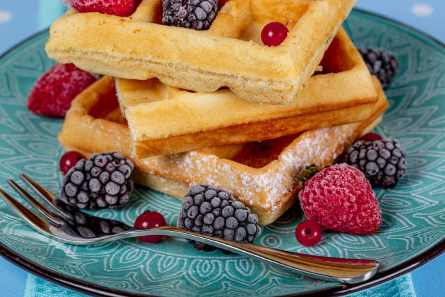 Close-up of Belgian waffles with berries on a blue plate with a fork