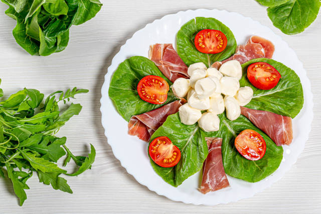 Top view salad with jamon, mozzarella, tomatoes and herbs on a white plate