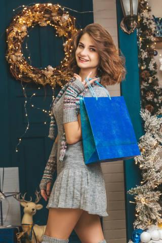 Happy girl with blue gift bag posing near door
