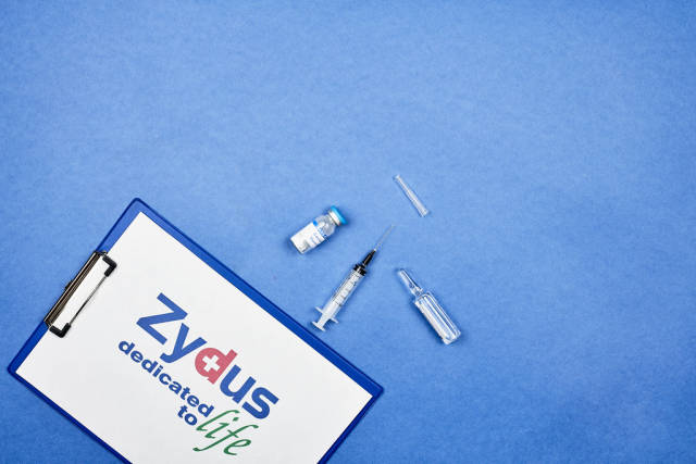 Clipboard with logo of Zydus Cadila, ampoule and syringe for Covid-19 vaccine on blue background
