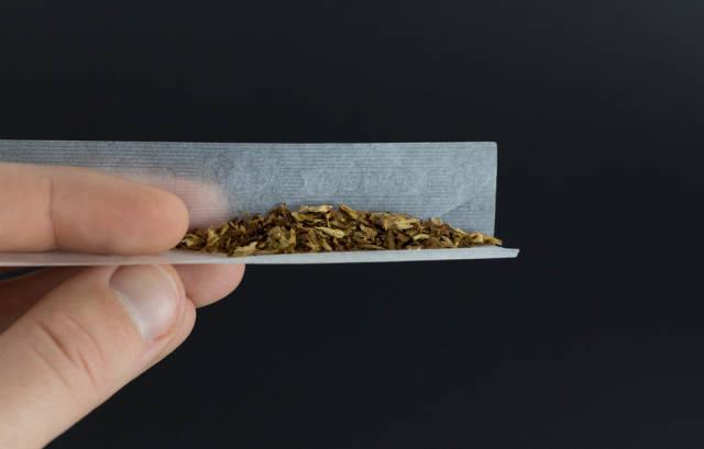 A man rolling tobacco cigarette
