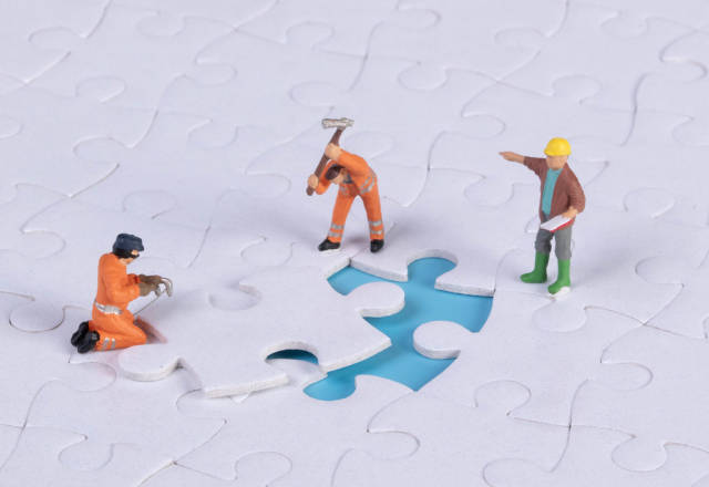 Miniature people team trying to complete the last jigsaw puzzle piece. Teamwork concept