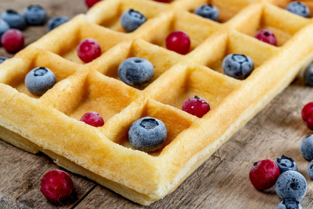 Homemade waffles with berries on wooden background, close up