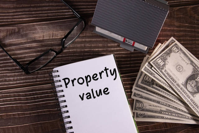 Small house with money and notebook with Property value text