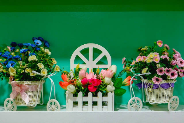 Miniature floral decoration on green wall