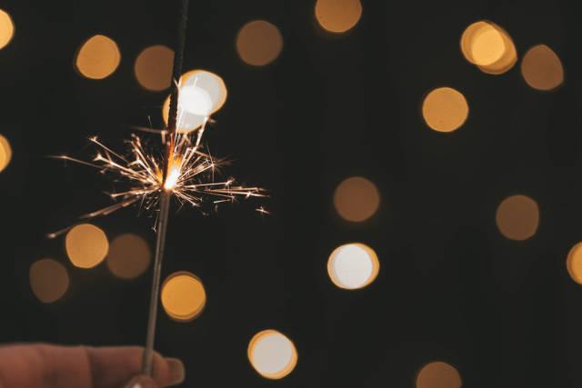 Sparkler in hand on golden bokeh background